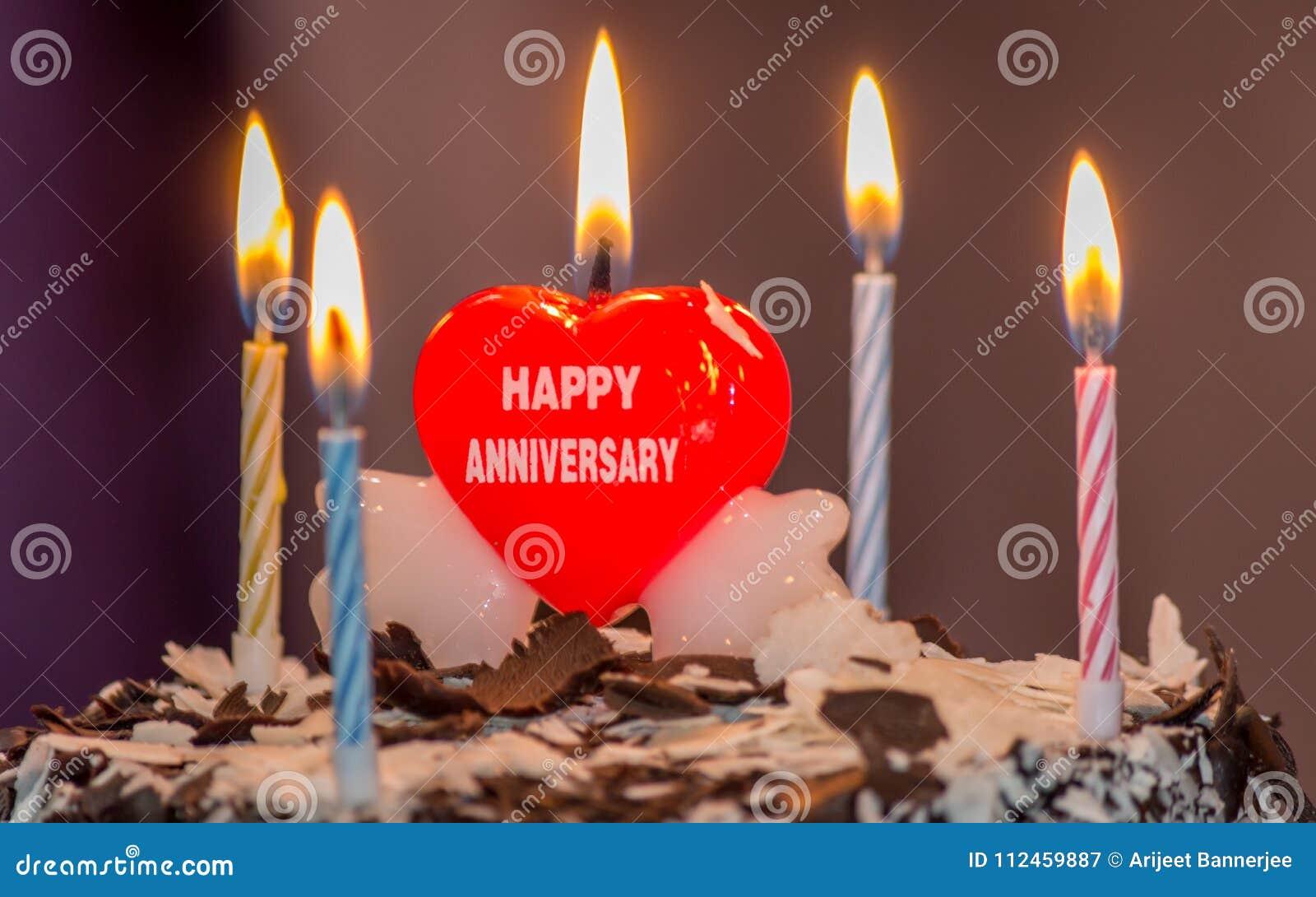 En célébrant l anniversaire de mariage avec un beau coeur formez la bougie sur le gâteau