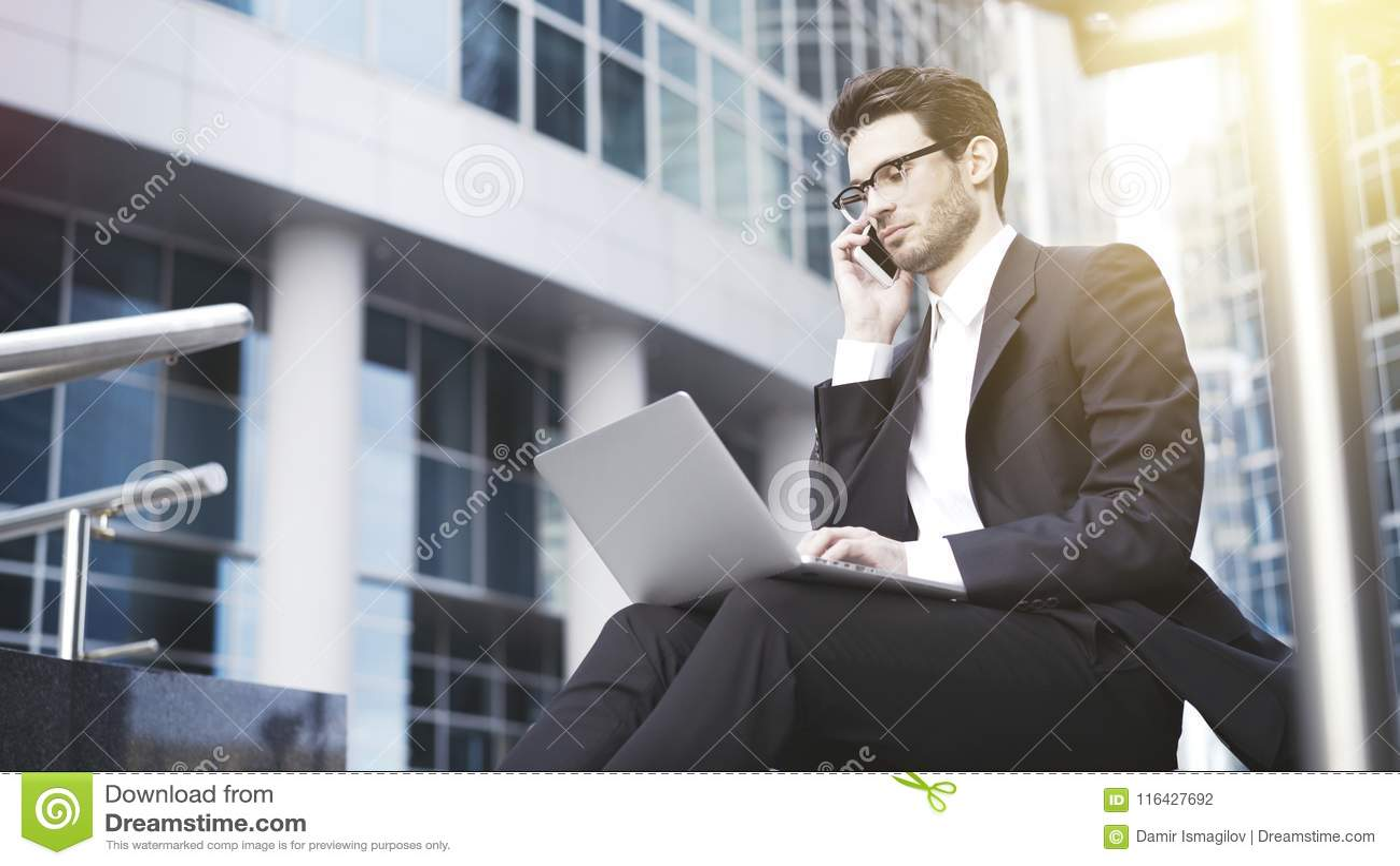 En closeup av den unga stiliga affärsmannen med bärbara datorn som har en appell