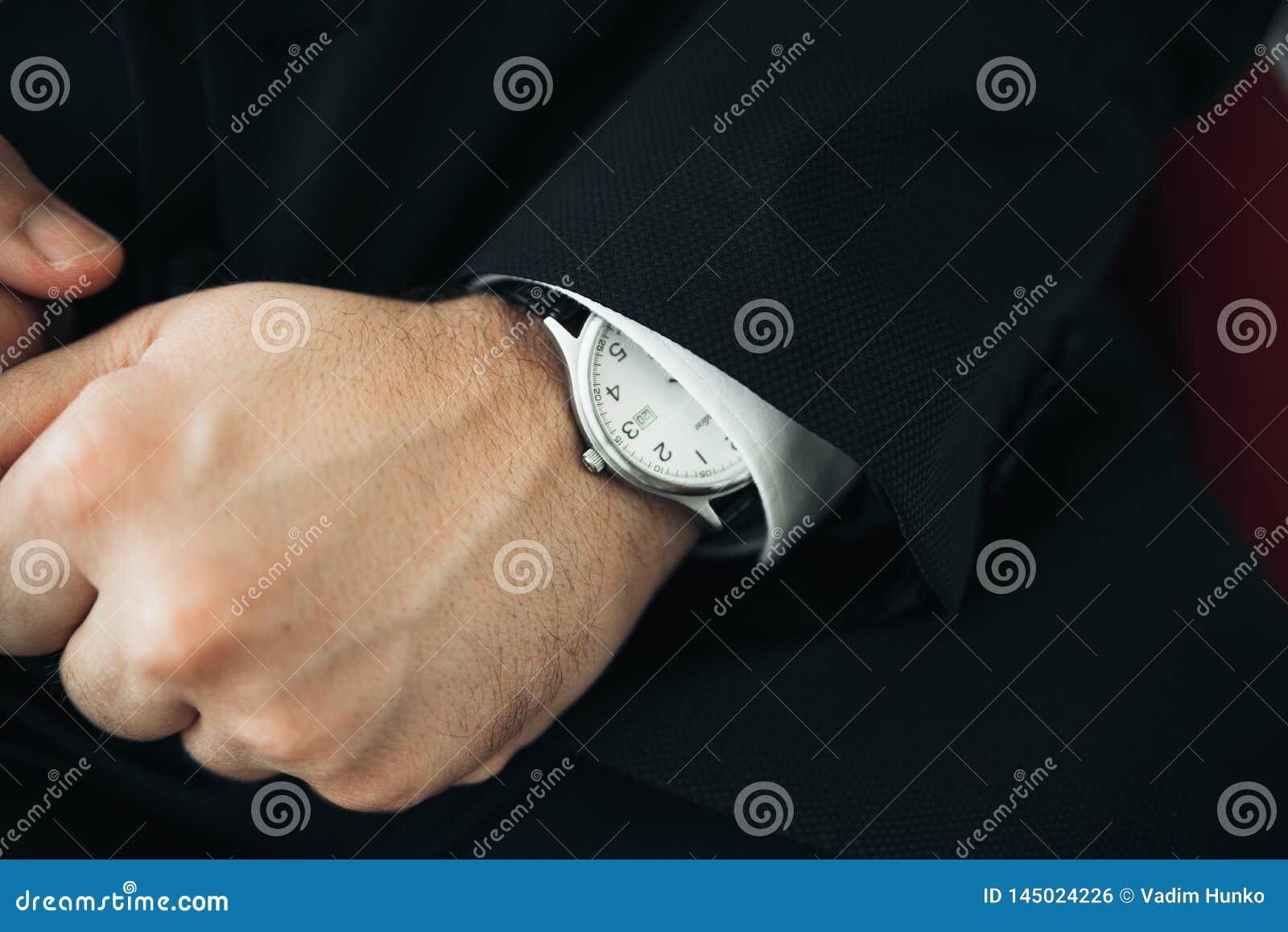 En closeup av en klocka med piskar armbandet p? mannens hand