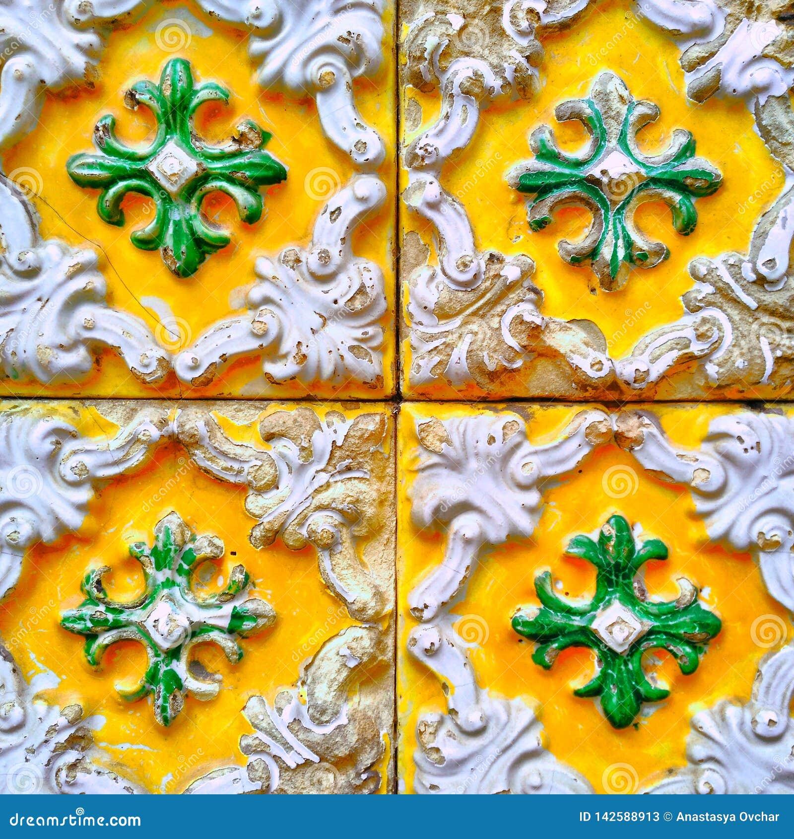En closeup av ljusa färgglade portugisiska tegelplattor med att smula emalj