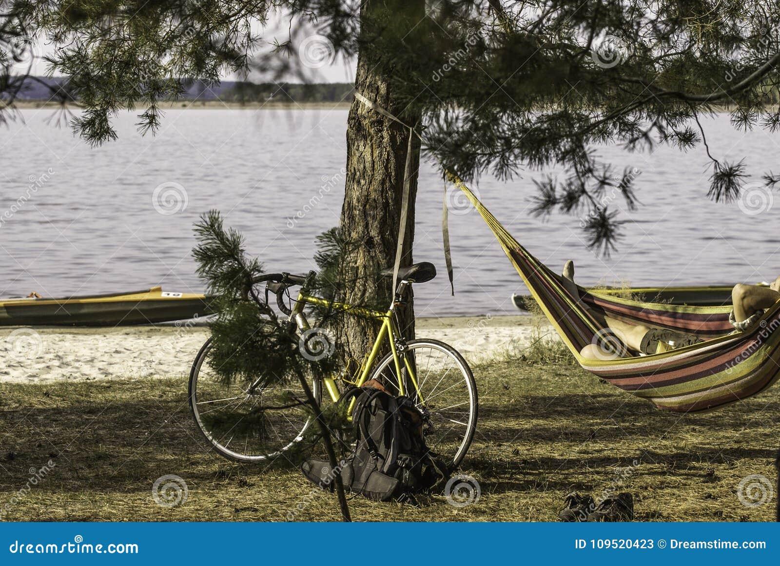 En cykel nära sörja på flodbanken, en cyklist som vilar i en hängmatta