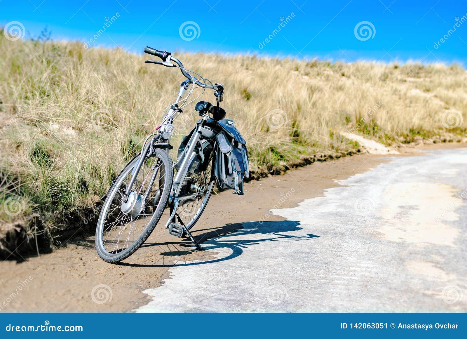 En cykel som parkeras längs en kust- väg med dyn på bakgrunden sommar för snäckskal för sand för bakgrundsbegreppsram semester Cy