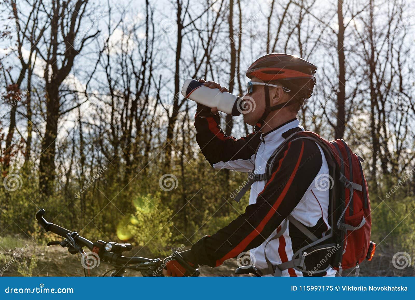 En cyklist i sportswear är dricksvatten från en flaska