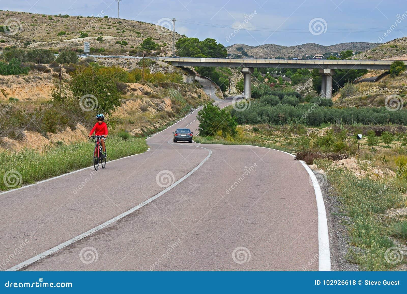 En cyklist som rider upp en kulle, i att bedöva landskap