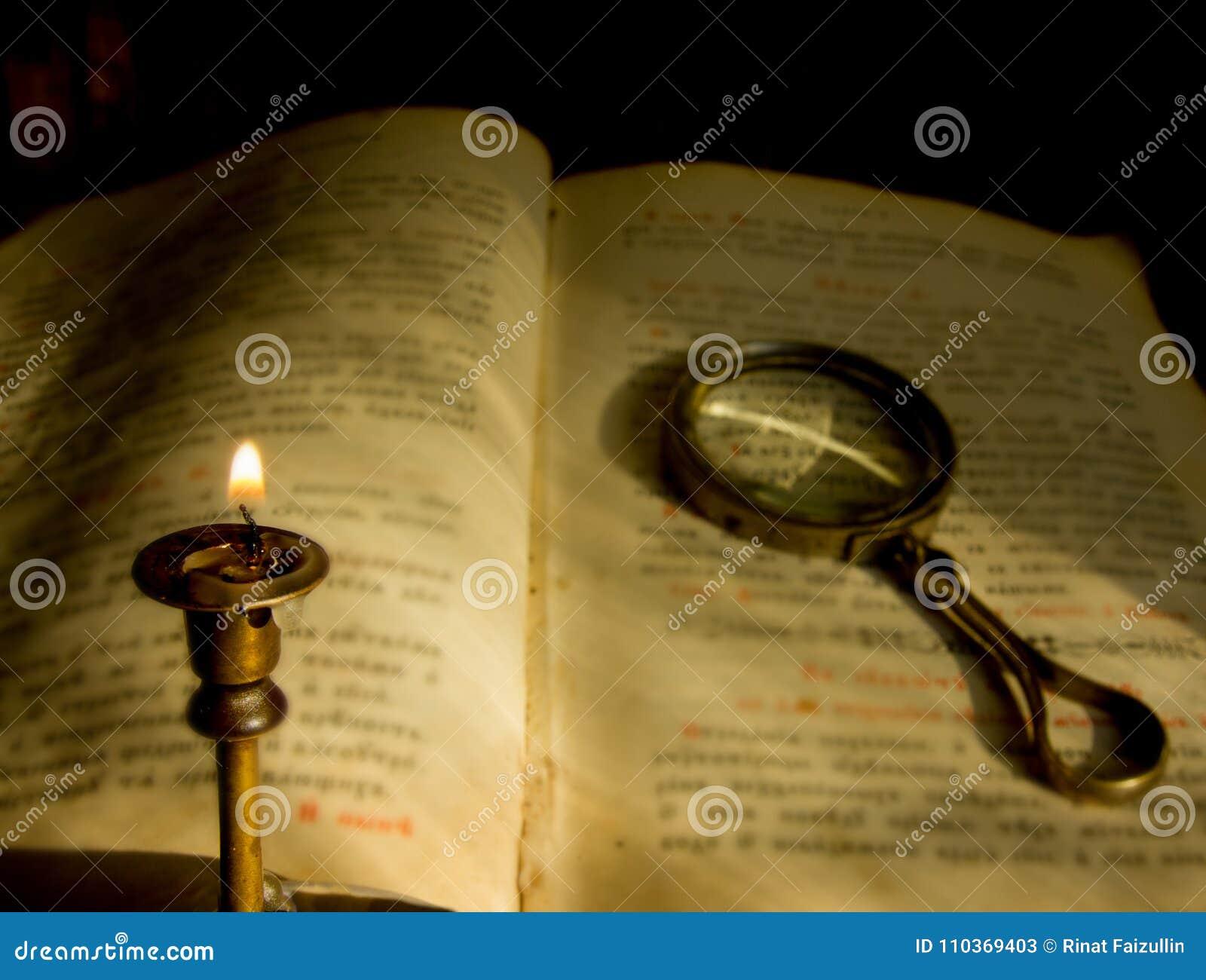 En döstearinljus och en gammal bönbok med ett förstoringsglas
