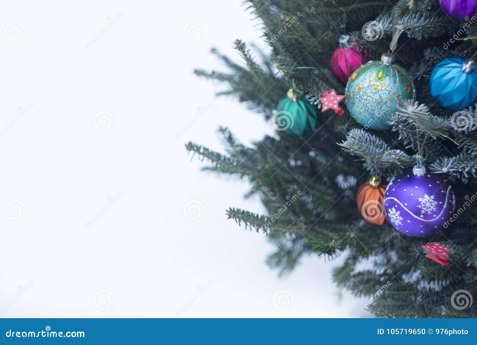 En dekorerad julgran utanför med färgrika struntsaker som göras av exponeringsglas