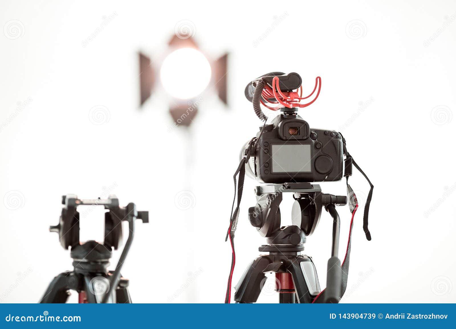 En digital videokamera med en mikrofon på en tripod på en vit bakgrund, en ljus strålkastare i bakgrunden