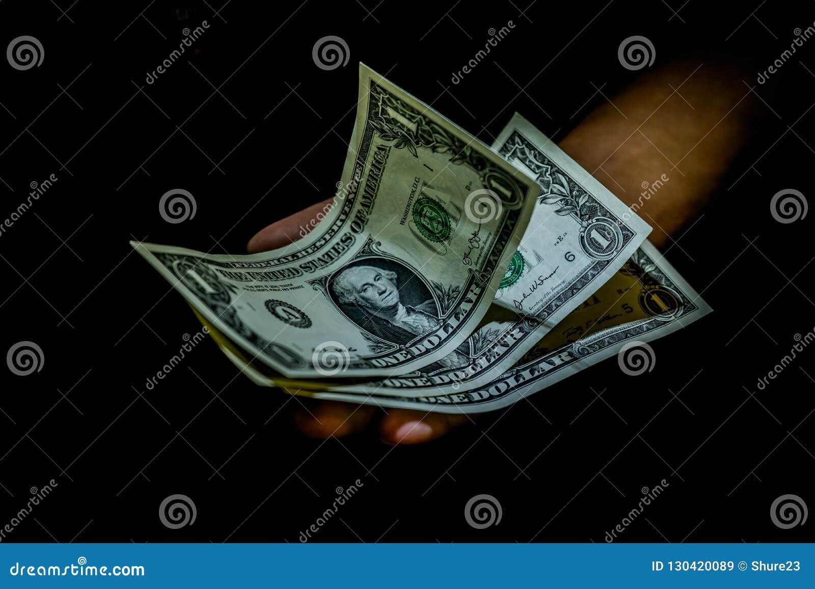 En dollar fakturerar i handen av en person som isoleras på svart