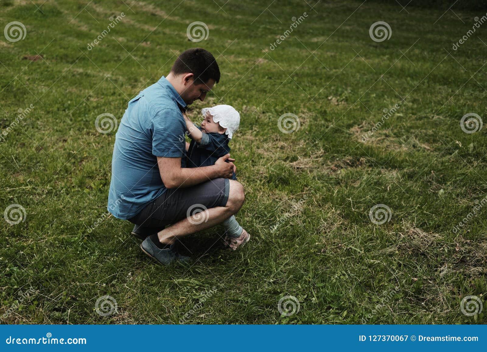 En dotter och en fader som huging i en parkera