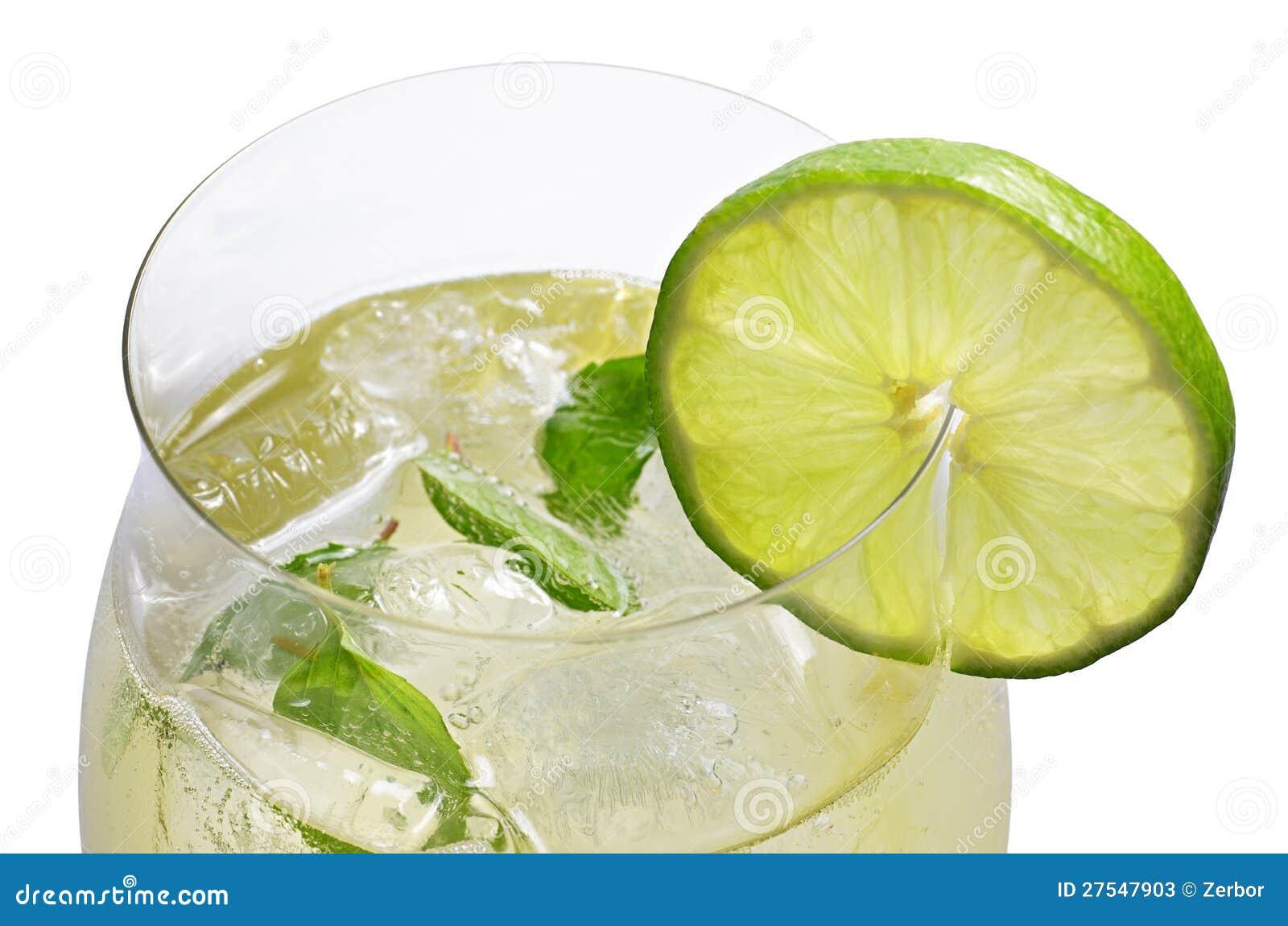 En drink med limefrukt och minten i ett wineexponeringsglas