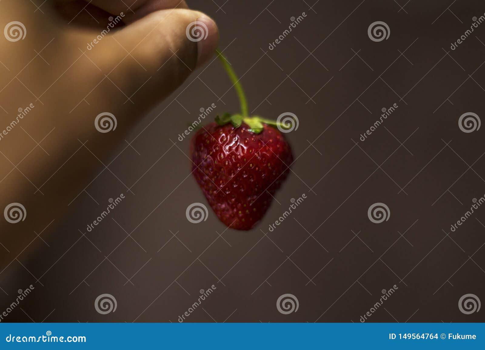 En el crepuscular un hombre est? sosteniendo sexual las fresas en su mano