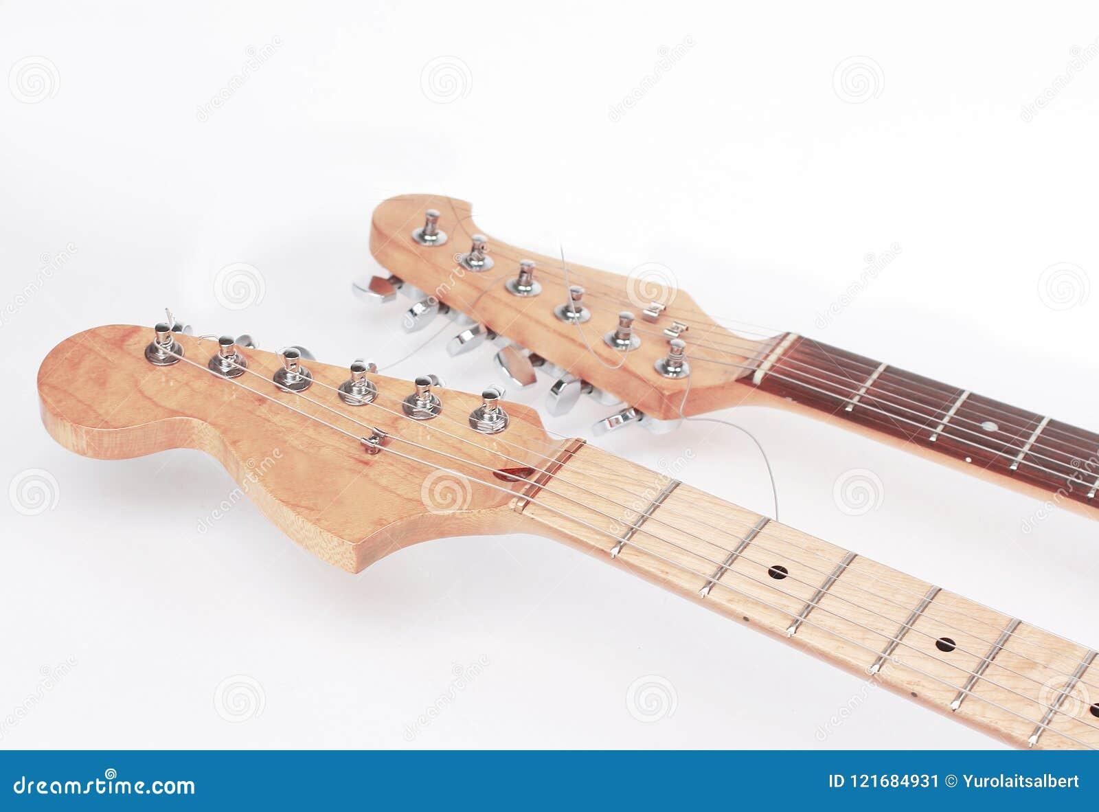 En el primero plano el fretboard de una guitarra acústica aislante