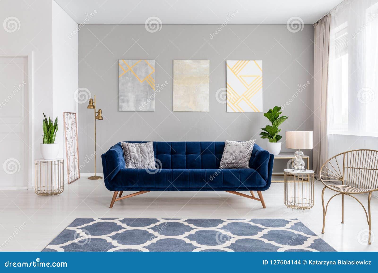 En elegant marinblå soffa i mitt av en ljus vardagsruminre med guld- metallsidotabeller och tre målningar på en grå färg