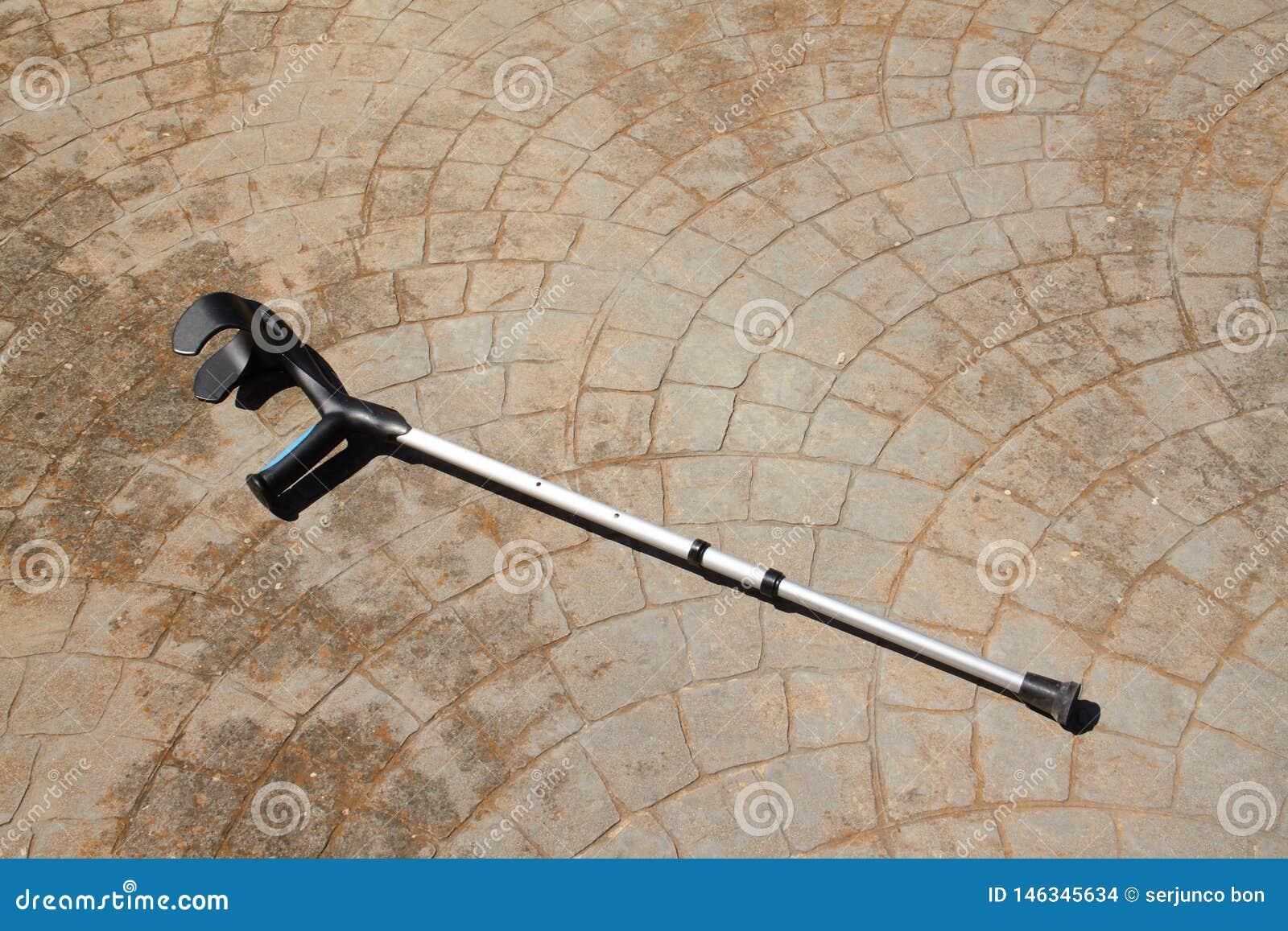 En enkel krycka på ett konkret golv som väntar på dess förlamade ägare