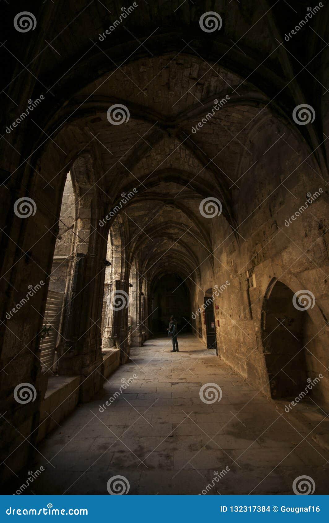 En enkel turist ser omkring under bågarna av den Palais desen Archevêques i Narbonne i söderna av Frankrike