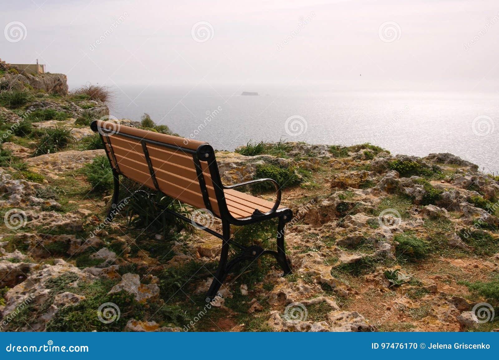 En ensam bänk på en stenig havkust