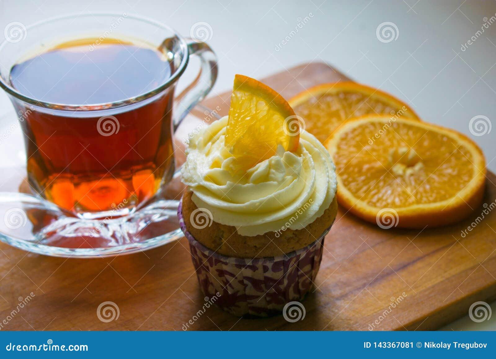 En exponeringsglaskopp te, en muffin med orange skivor på ett trämagasin