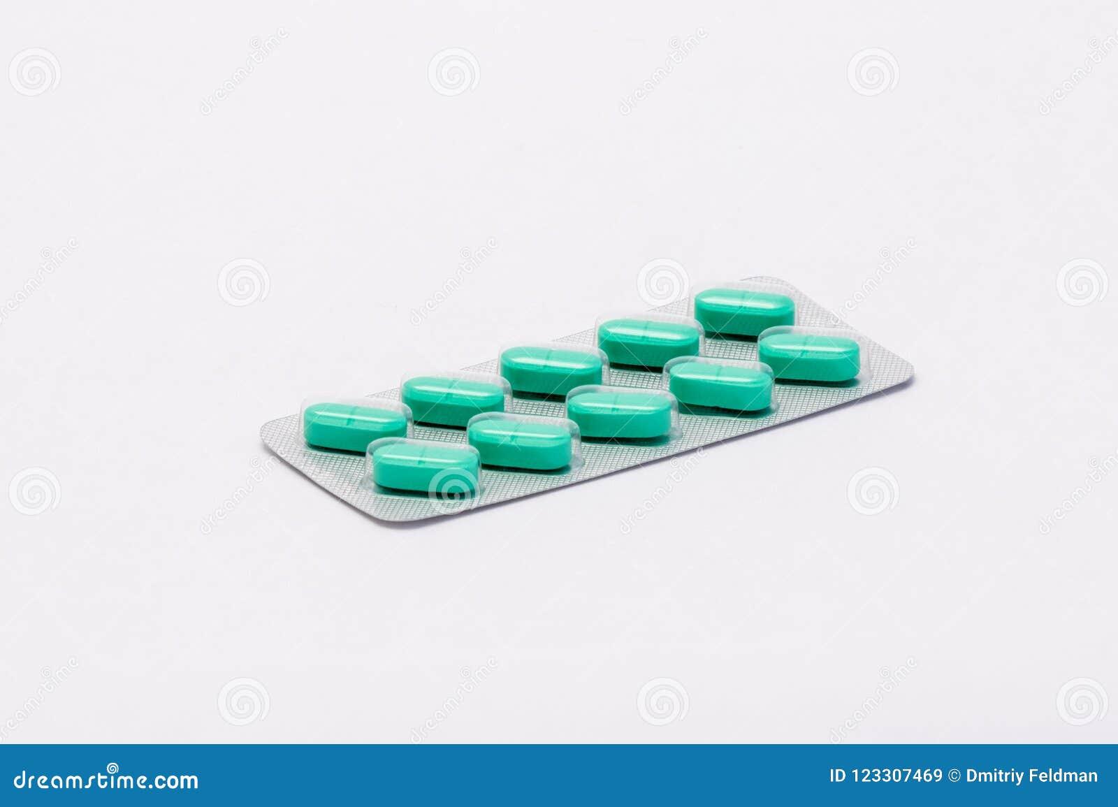 En färdig förseglad packe med gröna rektangulära preventivpillerar ligger på en vit bakgrund