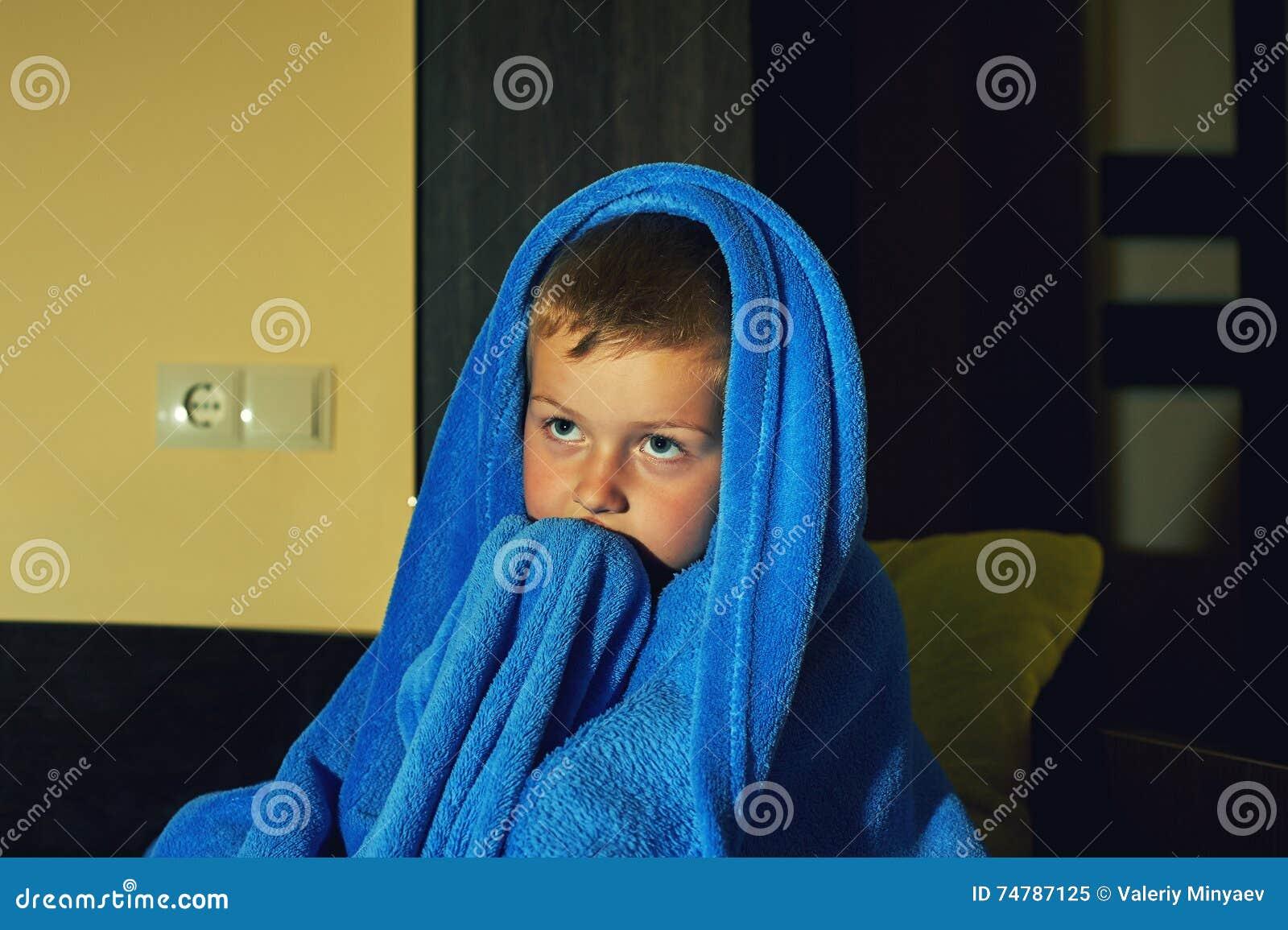 En förskräckt pys som är rädd i säng på natten, barndom fruktar