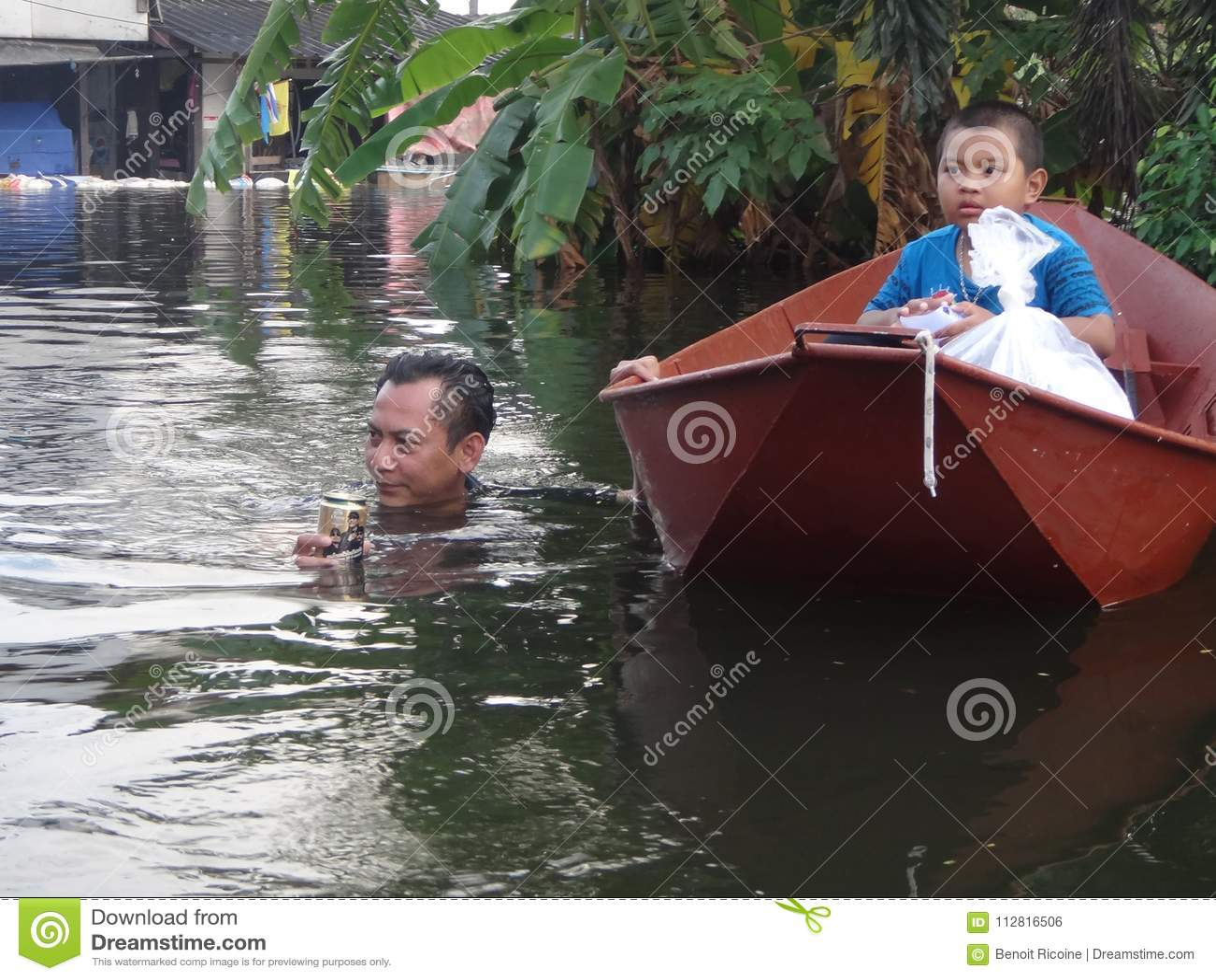 En fader tar hans son till säkerhet i en översvämmad gata av Pathum Thani, Thailand, i Oktober 2011