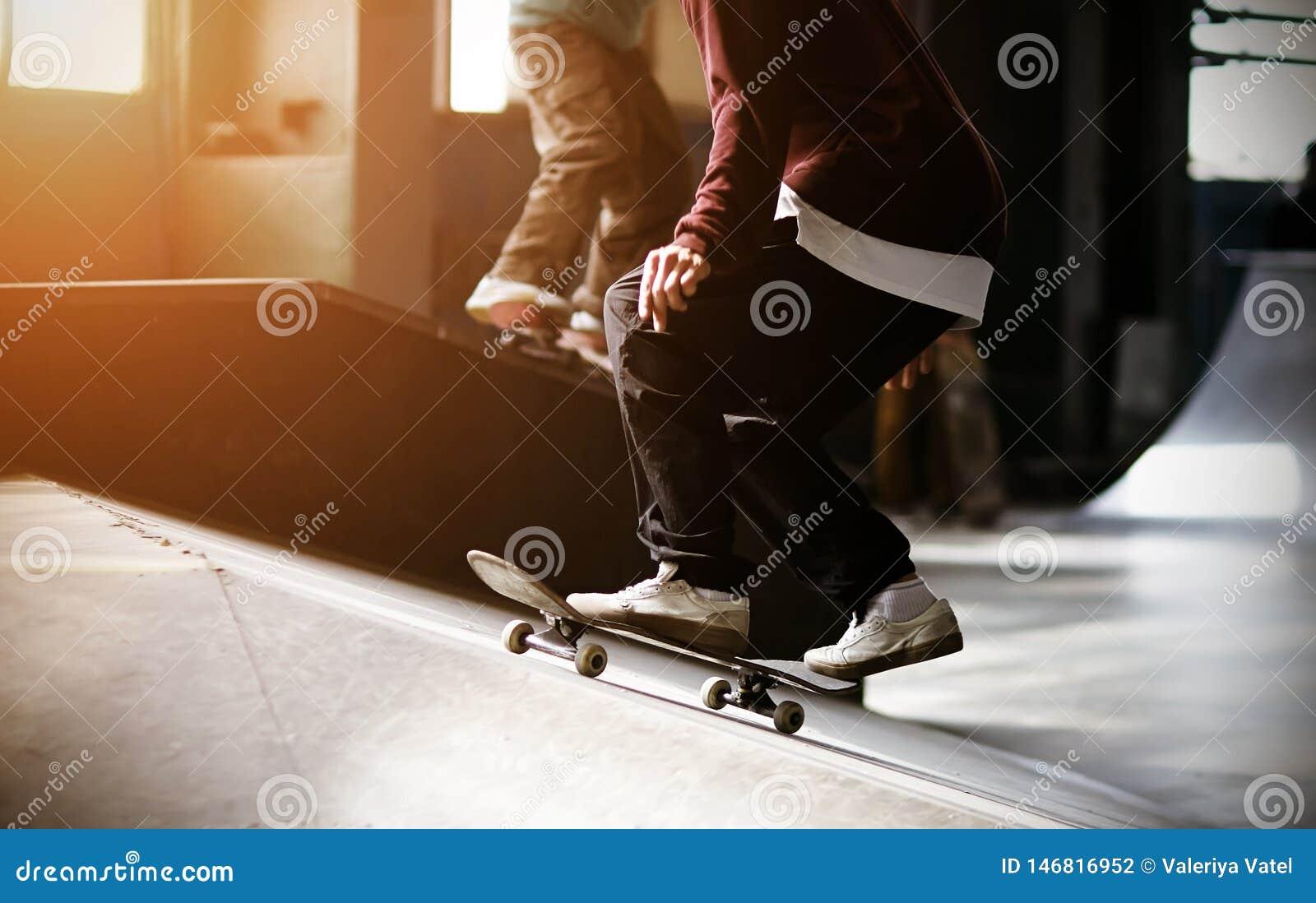 En fashionably klädd grabb rider en skateboard på en ramp och ska göra ett hopp