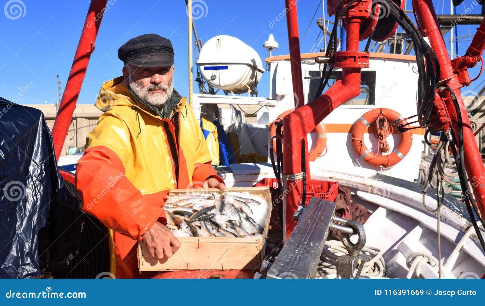 En fiskare med en fiskask inom en fiskebåt