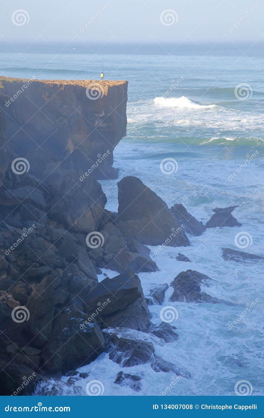 En fiskare som metar ovanför de höga klipporna nära den Amoreira stranden Aljezur, Costa Vicentina, Algarve