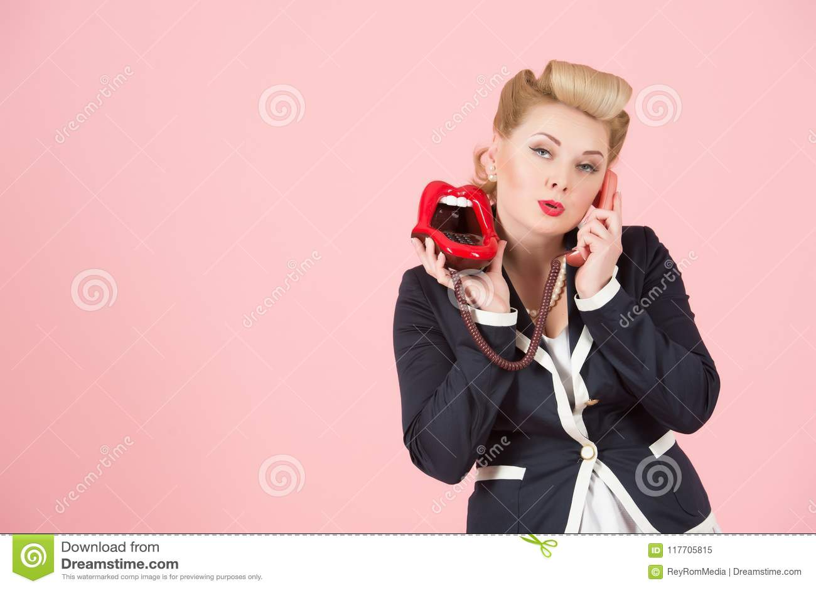 En flörta stående av den blonda flickan med telefonen i utvikningsbildsmink med copyspaceområde för annonsering av textmeddelande