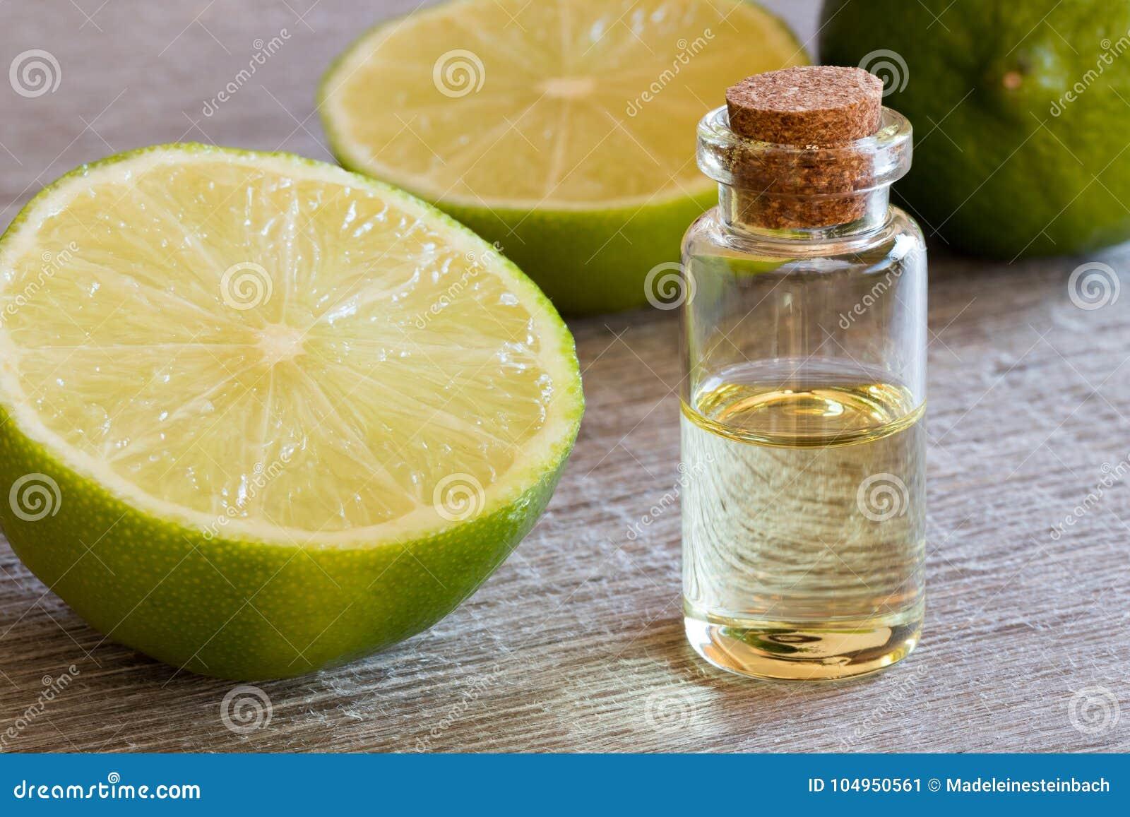 En flaska av nödvändig olja för limefrukt med nya limefrukter