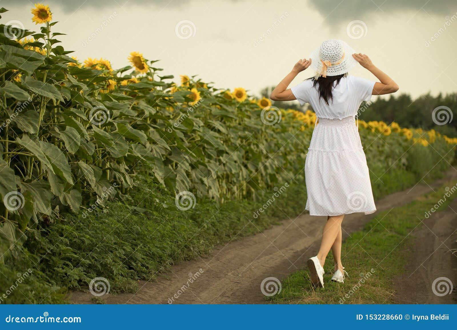 En flicka går på ett fält med solrosor