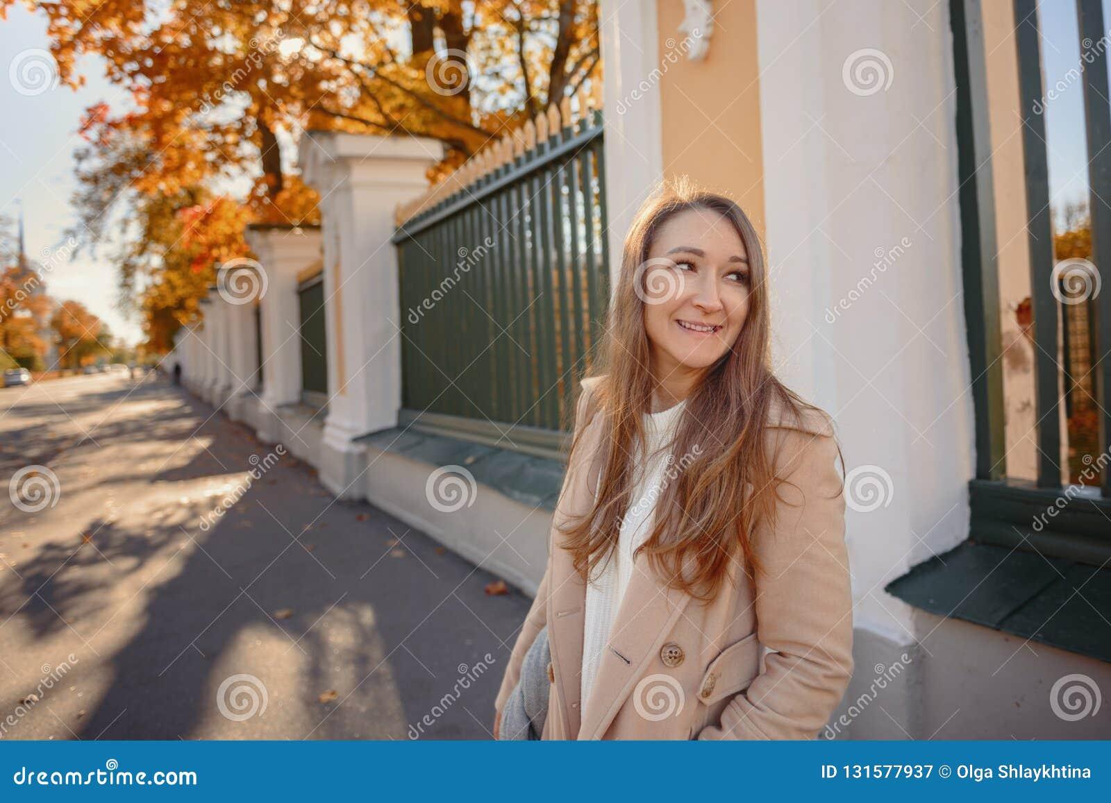 En flicka i ett beige lag och en svart klänning i hösten parkerar En sinnlig flicka med långt hår höstflickan låter vara yellow a
