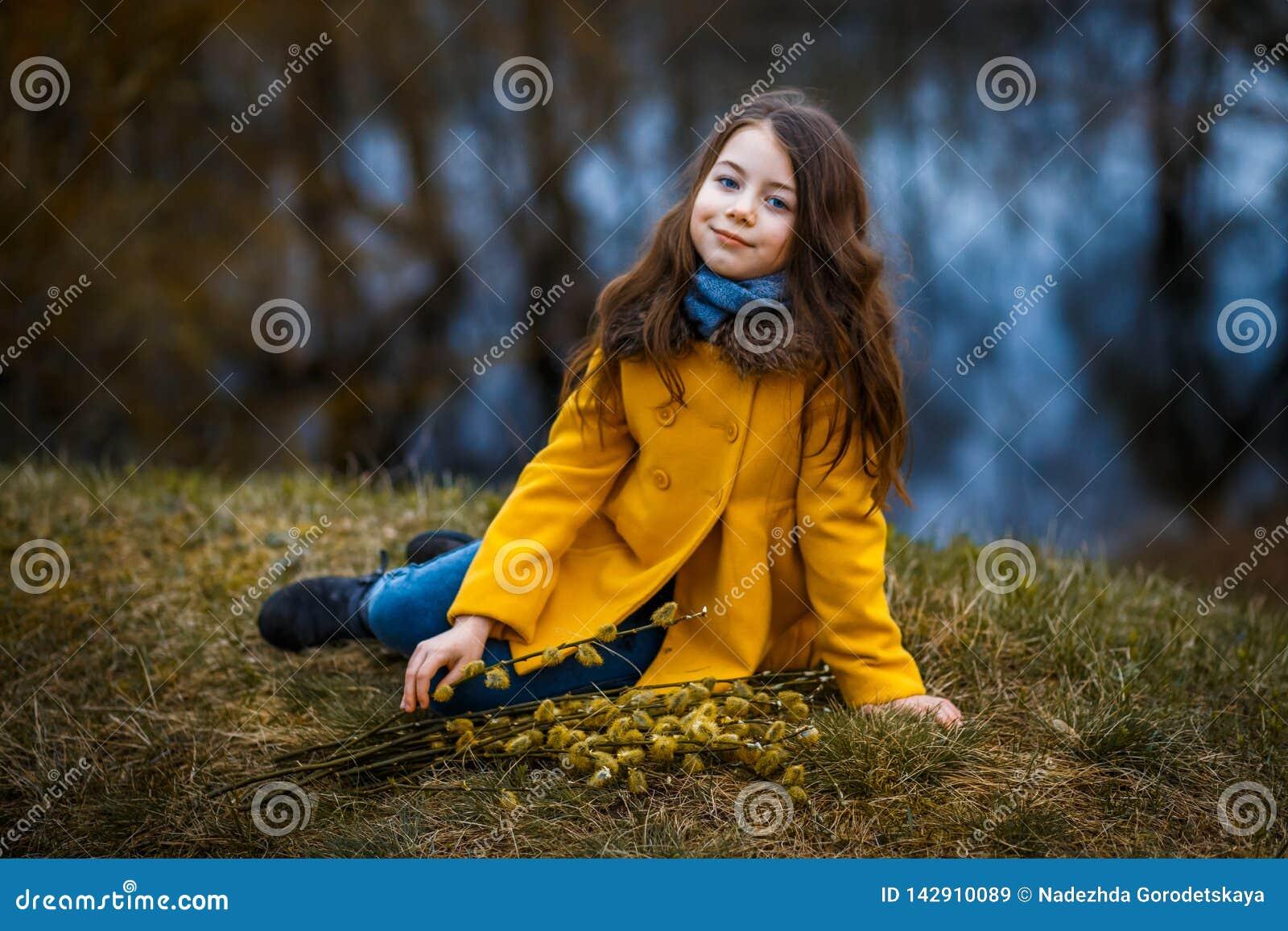 En flicka i ett gult lag i skogen i tidig vår med en pilfilial av ris En flicka som pälsfodrar fresheten eller högt vatten