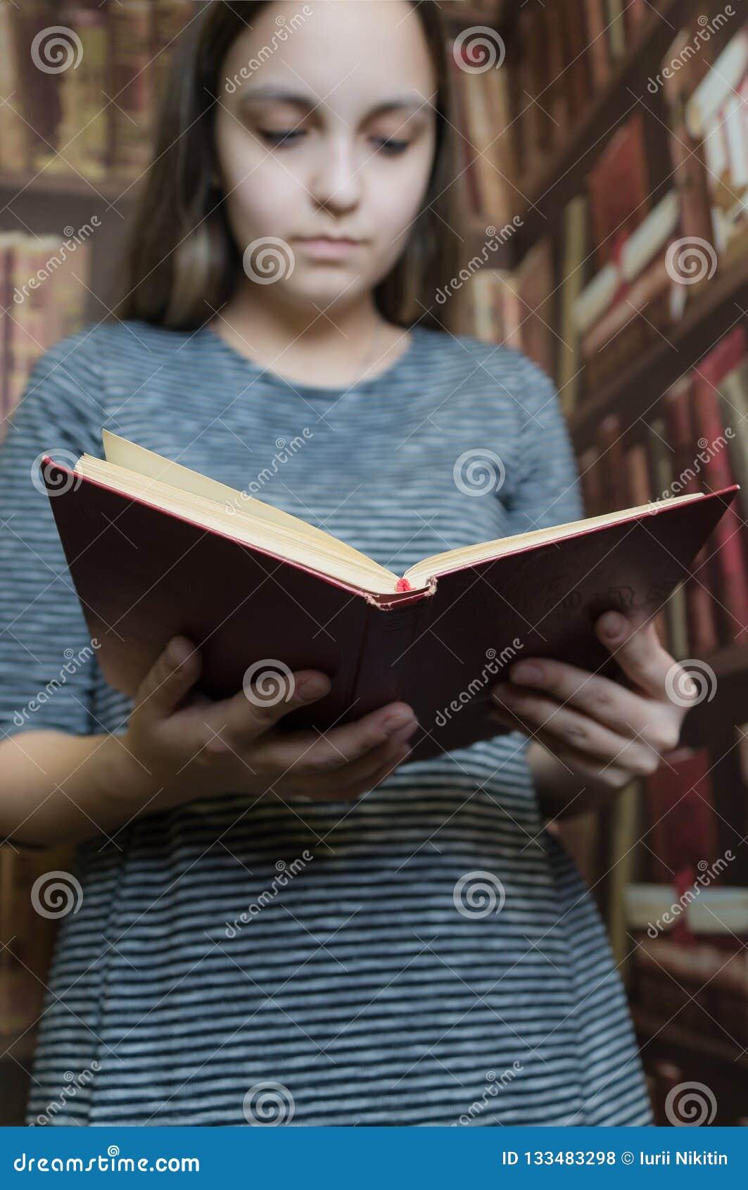 En flicka i en grå klänning som läser en bok i arkivet slapp fokus