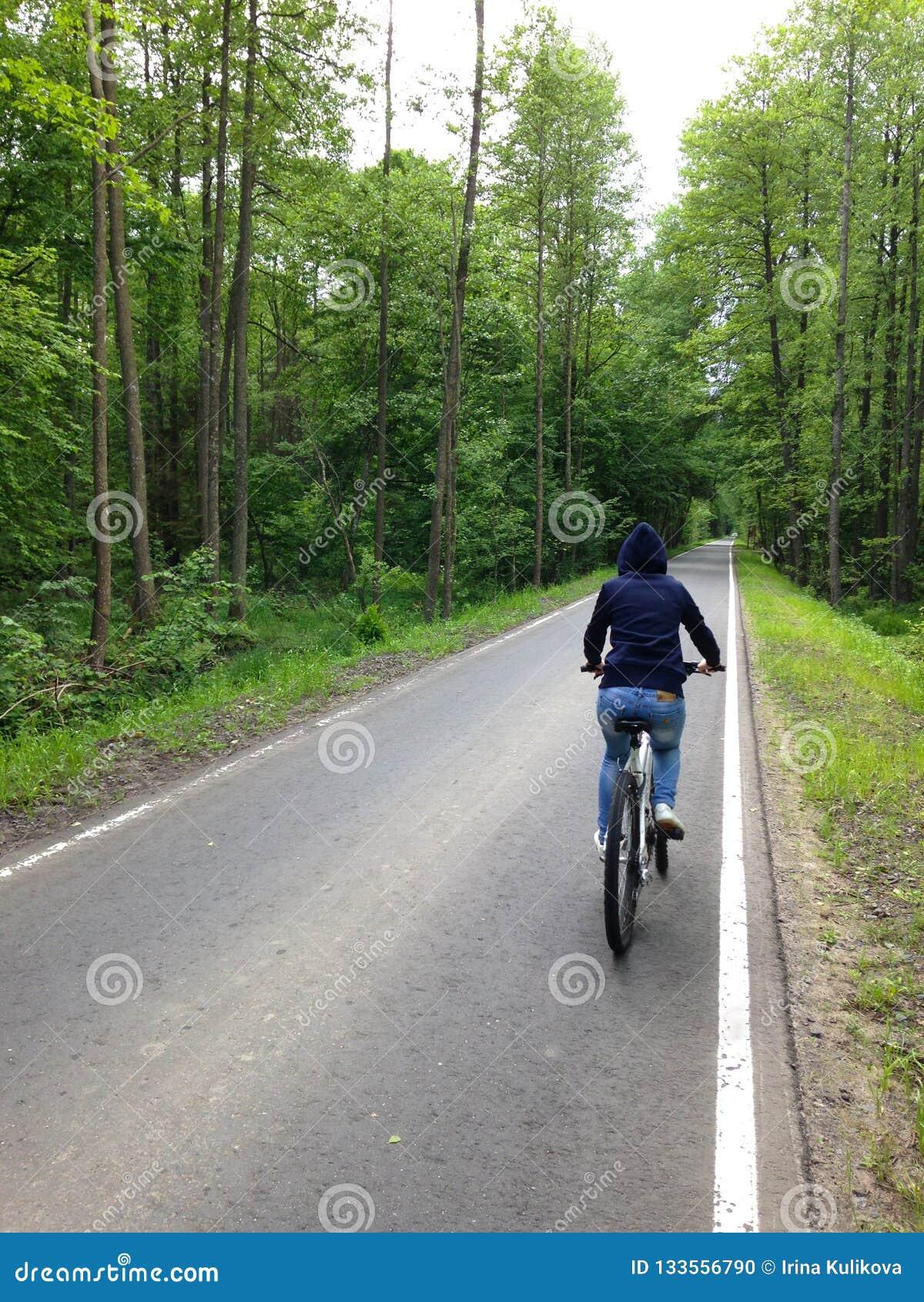 En flicka i en hoodie rider en cykel på en asfaltbana
