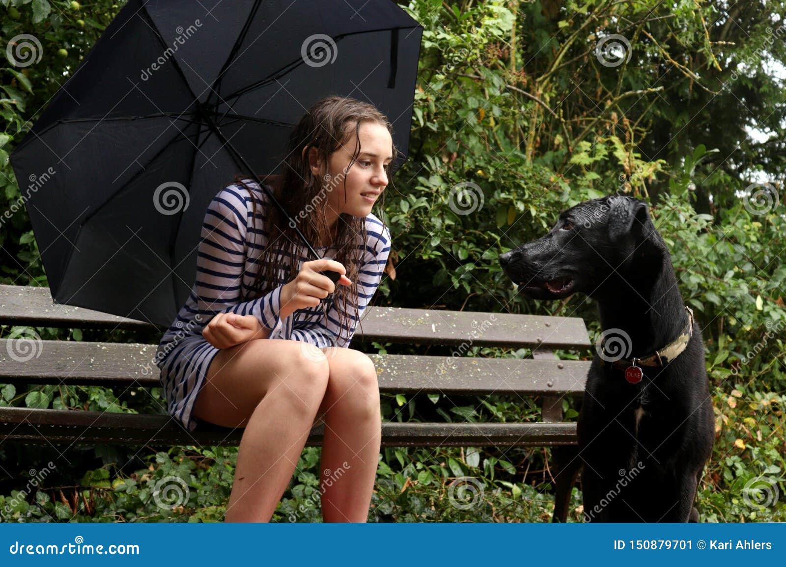 En flicka och hennes hund som spelar i regnet