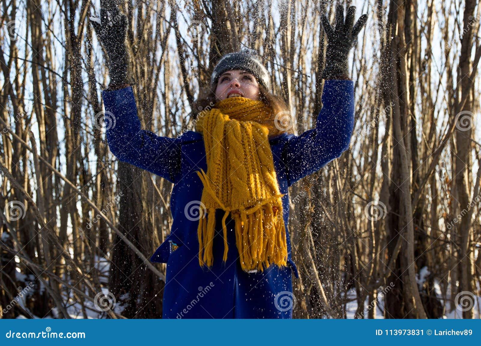 En flicka på en gå i parkera i vinter i ett snöfall Hon bär ett purpurfärgat lag och en grå hatt och gulinghalsduk