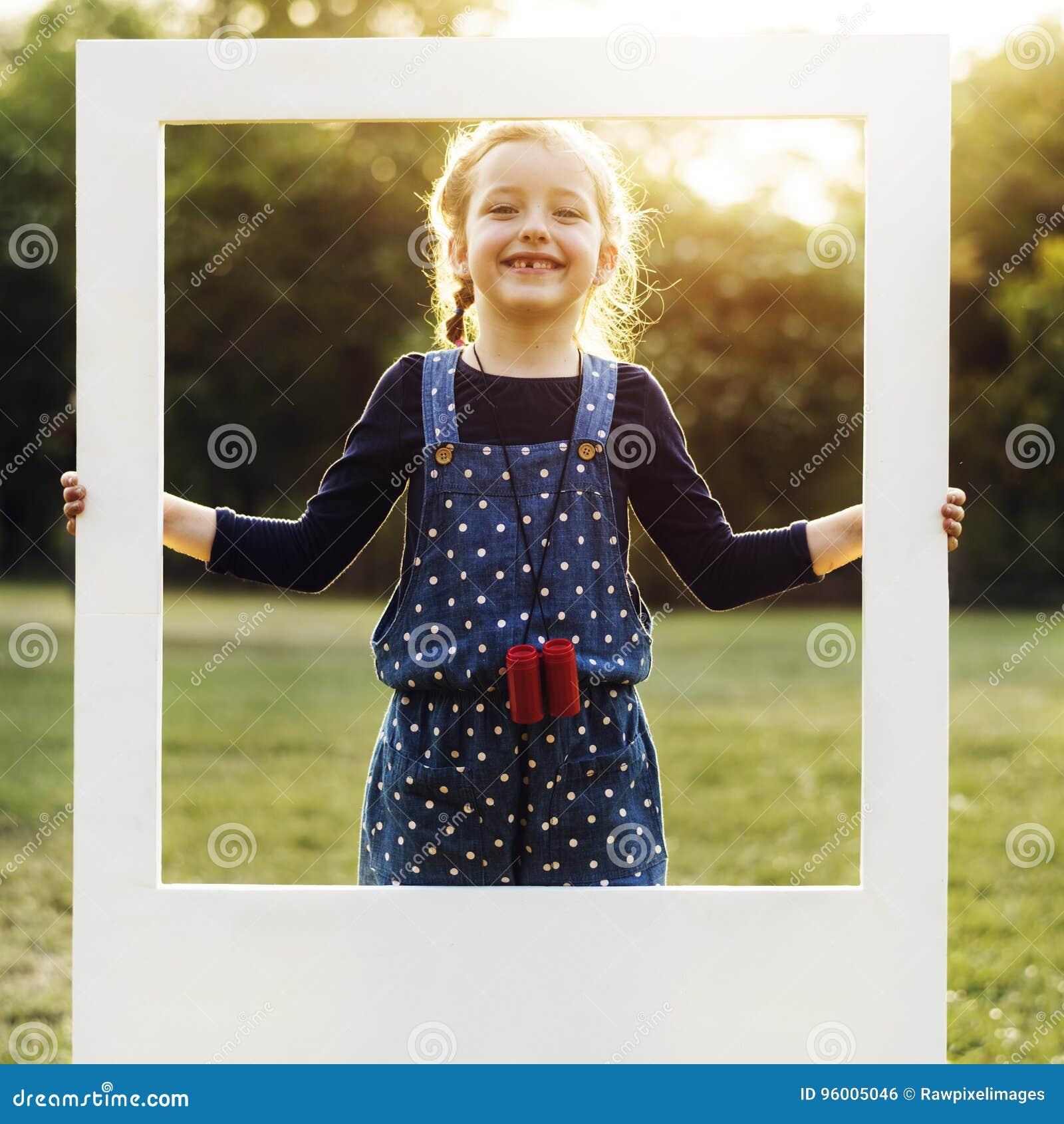 En flicka rymmer en ram i en parkera