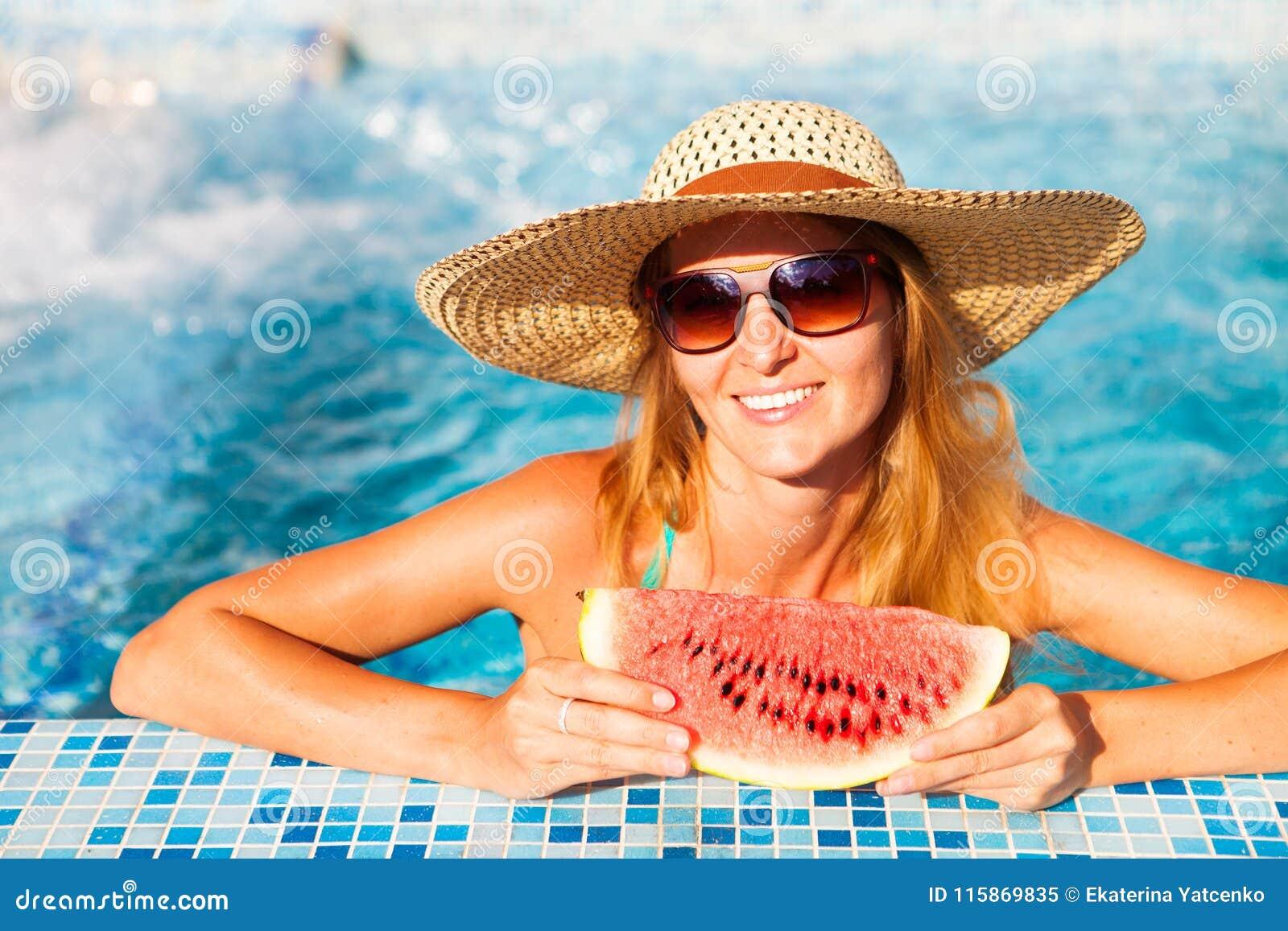 En flicka rymmer halva en röd vattenmelon över en blå pöl, avslappnande nolla