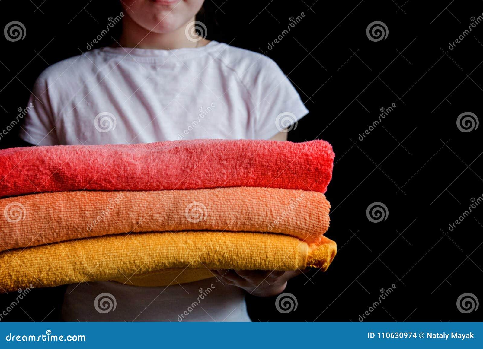 En flicka rymmer handdukar i deras händer