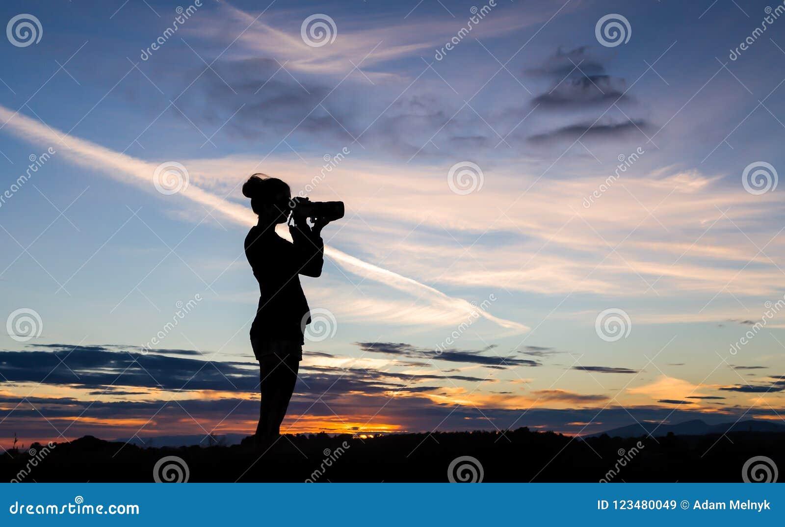 En flicka silhouetted mot en solnedgånghimmel som tar ett foto med en DSLR