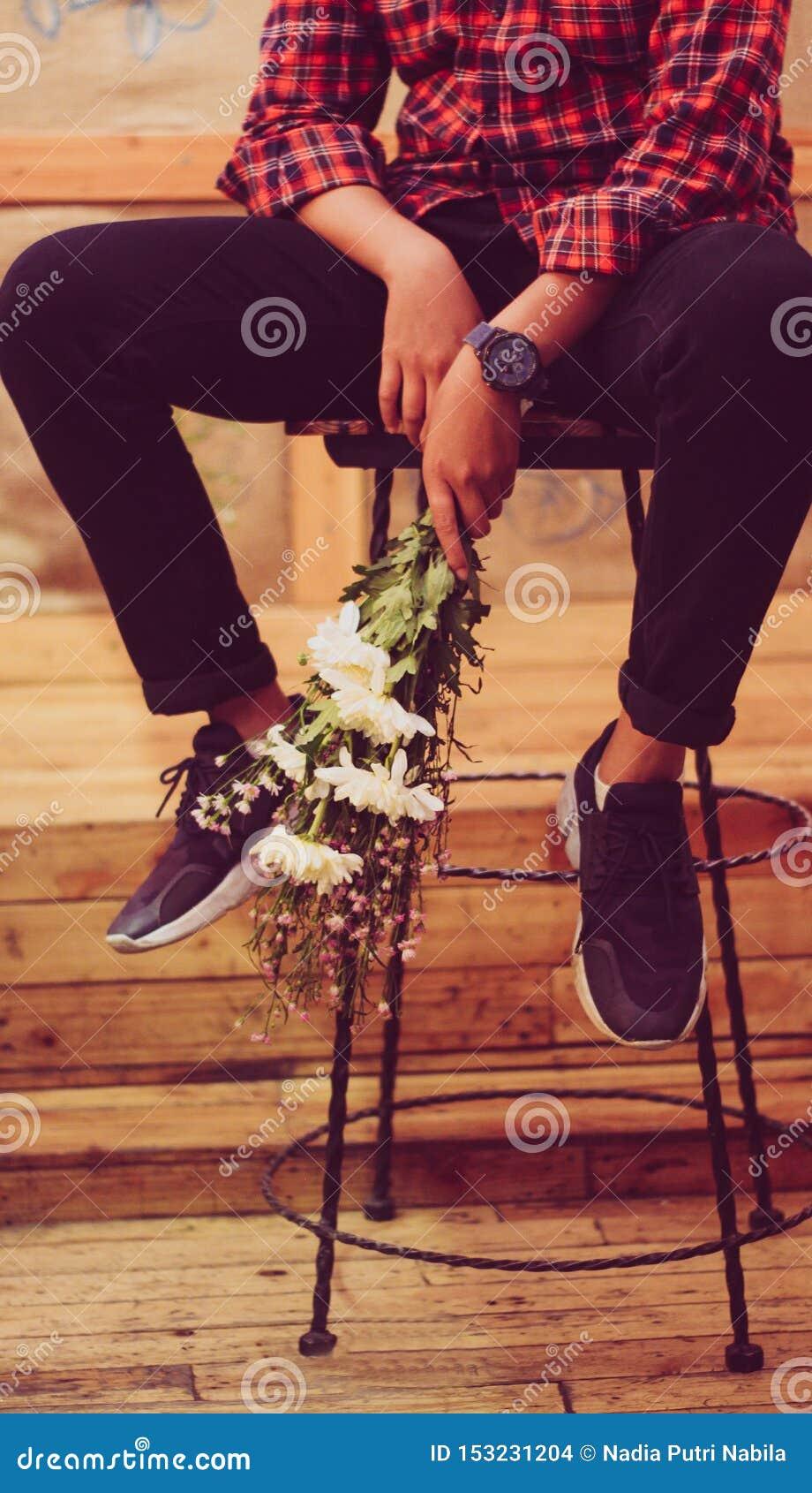 En flicka som rymmer en blommaboquet på stolen i en coffee shop