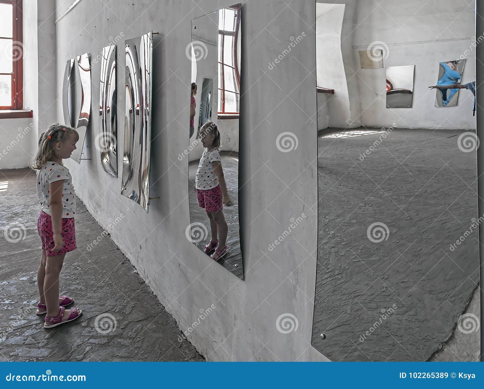 En flicka som ser hennes bild i den förvridna spegeln i korridoren av speglar