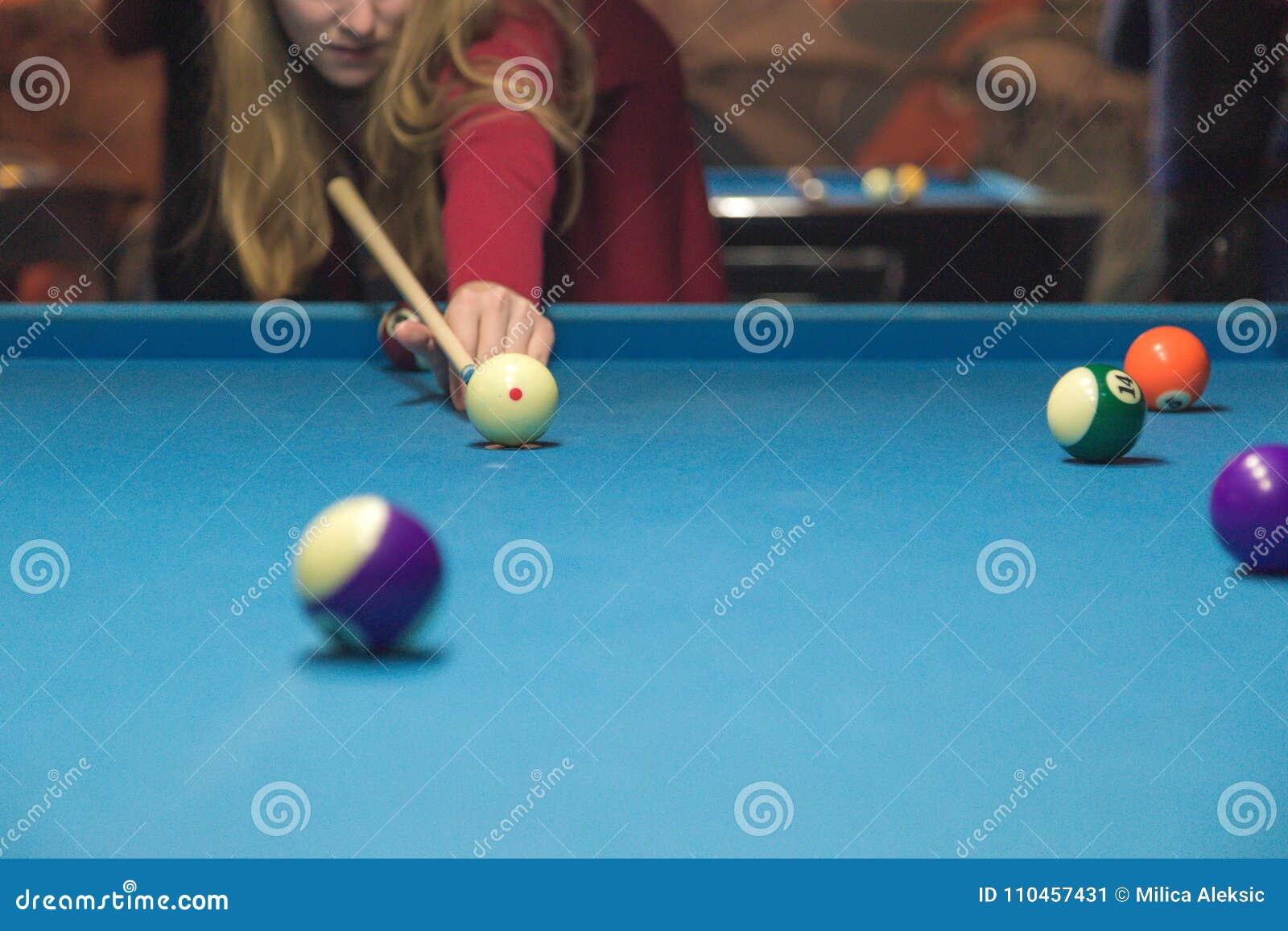 En flicka spelar en billiard på klubban