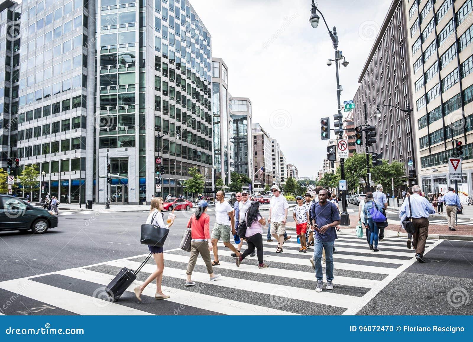 En folkmassa av folk som korsar en stadsgata på övergångsstället