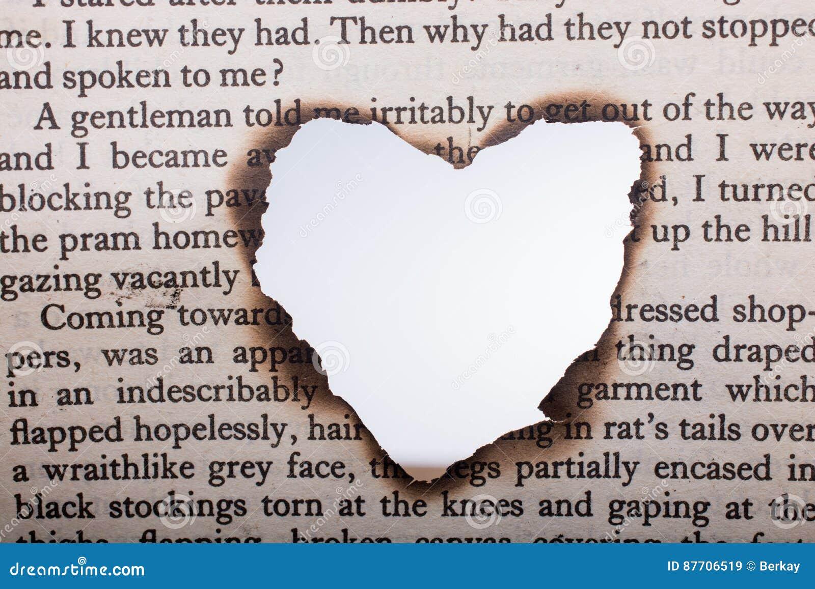 En forme de coeur brûlé hors du papier textoté