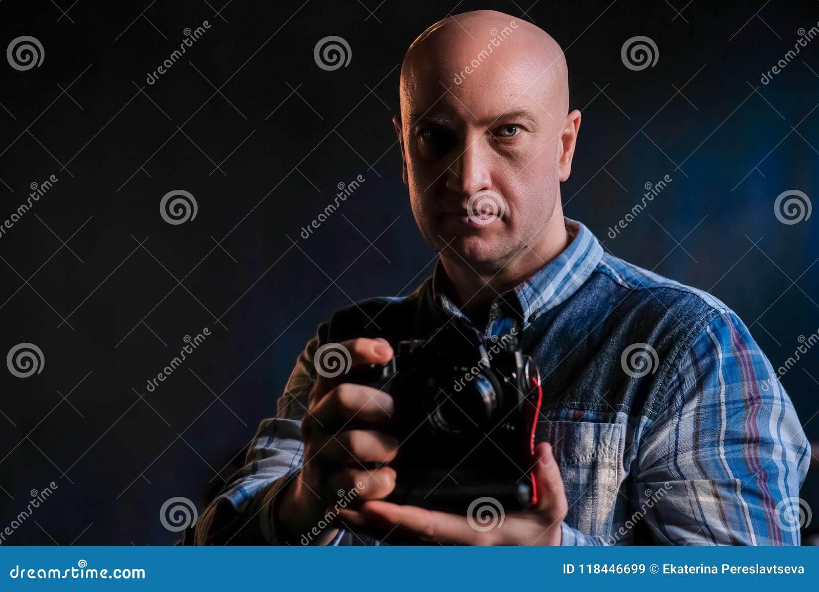 En fullvuxen man i en skjorta med en kamera i hans händer