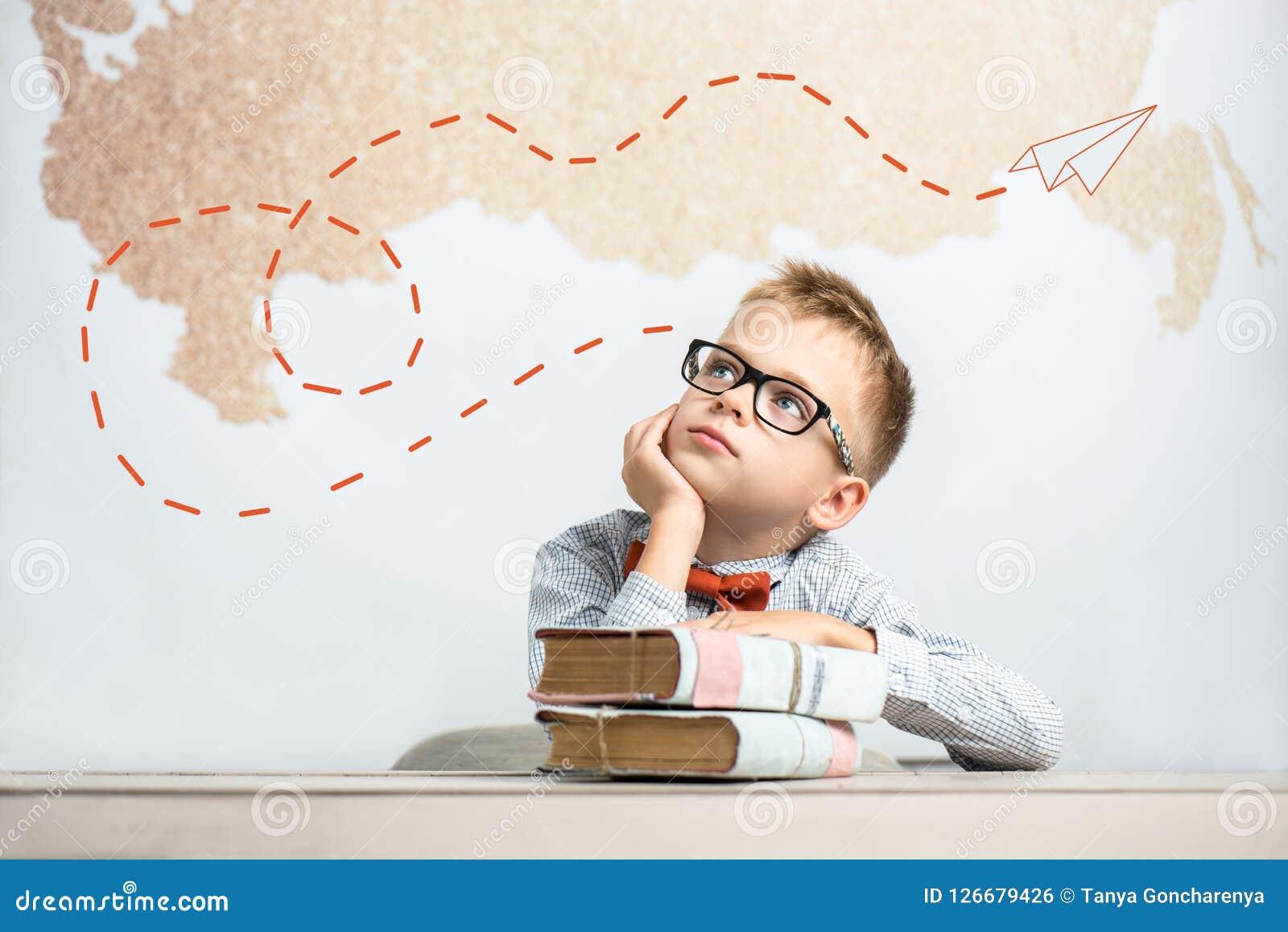 En fundersam skolpojke sitter på ett skrivbord med böcker