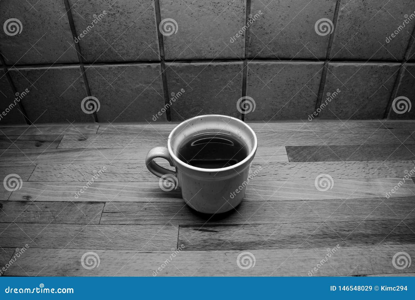 En fylld kopp te står på en träcountertop framme av en belagd med tegel vägg