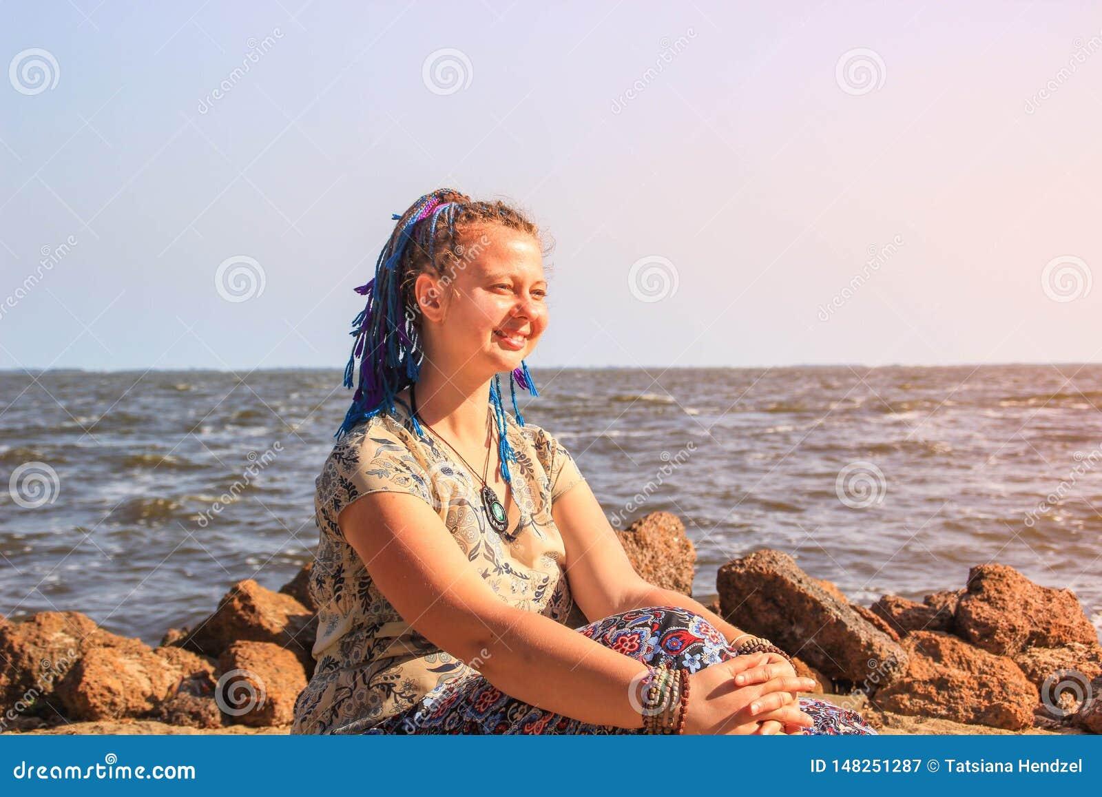 En fyllig ung vit flickahandelsresande med blått råttsvanshår sitter barfota på sanden mot bakgrunden av Lake Victoria