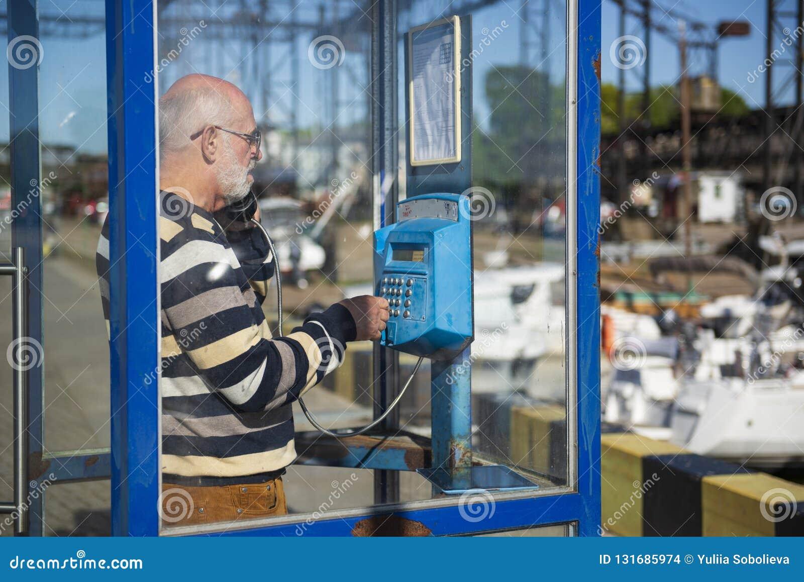 En gamal man kallar från en payphone